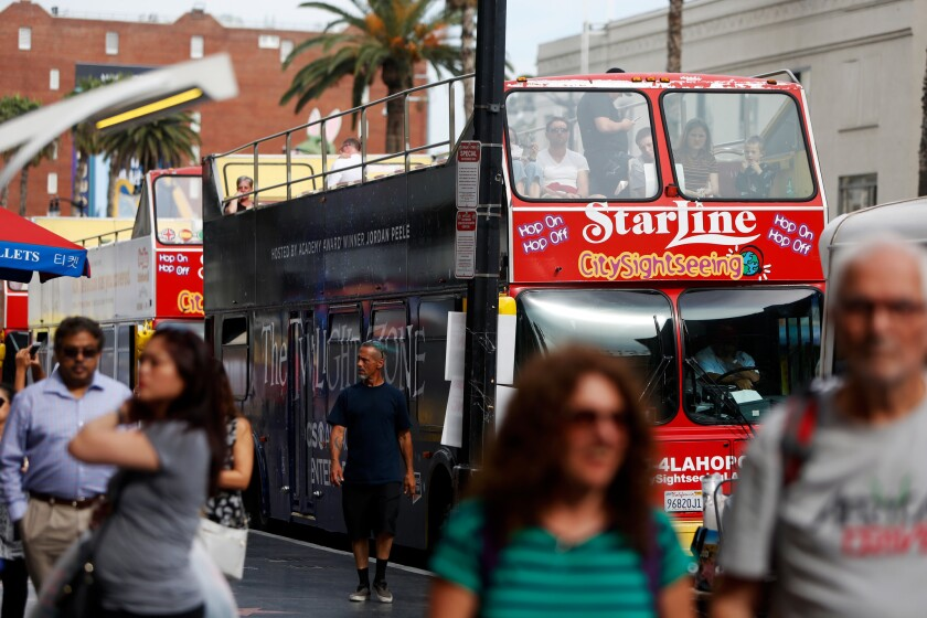 LOS ANGELES, CA-APRIL 8, 2019: People pass a Starline bus tour boarding area on Hollywood Blvd on Ap