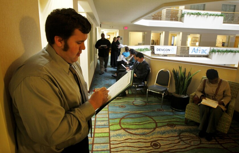 Job seeker Joseph McKay fills out a registration form at a HireLive job fair in December at a La Jolla hotel that featured 17 San Diego companies looking to hire. Eduardo Contreras • U-T