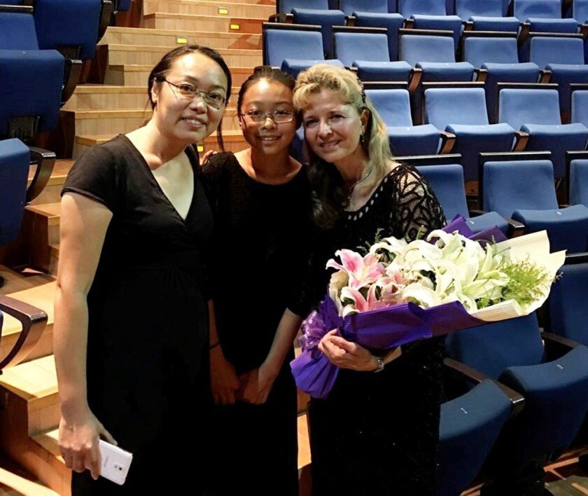 Artistic Director Ulli Reiner, right, with Lily Fan and her daughter May He at the Shanghai concert. He is Reiner's orchestra student at Twin Peaks Middle School.
