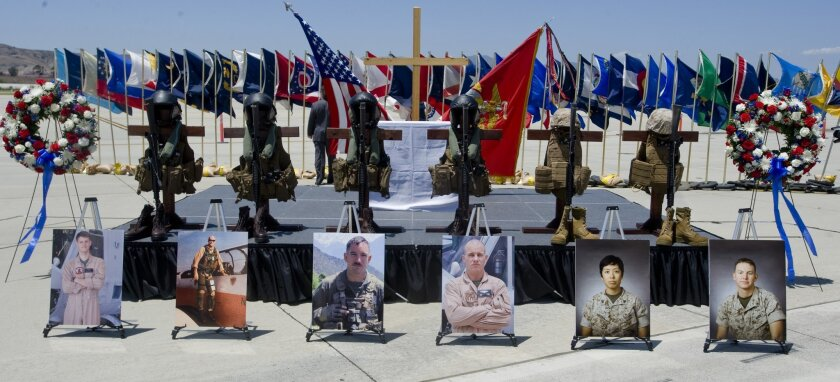 Photos of six Marines killed in a helicopter crash while on a rescue mission for earthquake victims in Nepal are displayed with flight vests, helmets, rifles and boots during a memorial service at Camp Pendleton, Calif., Wednesday, June 3, 2015. The six were, from left, Capt. Dustin R. Lukasiewicz,