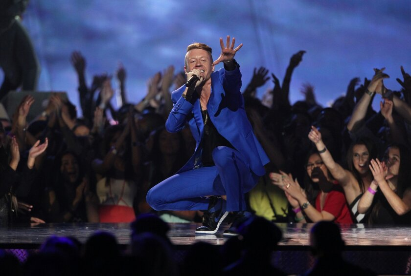 """FILE - In this April 14, 2013 file photo, Macklemore performs """"Can't Hold Us"""" at the MTV Movie Awards in Sony Pictures Studio Lot in Culver City, Calif. (Photo by Matt Sayles/Invision /AP)"""