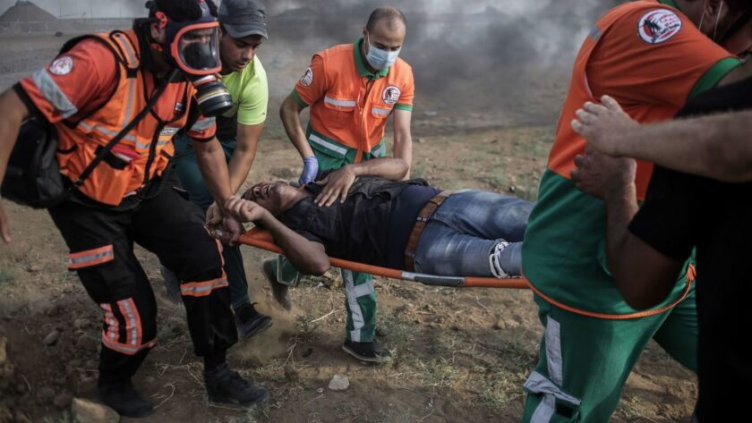 Palestinians carry a wounded protester during clashes with Israeli troops along the Israel-Gaza Strip border Friday.