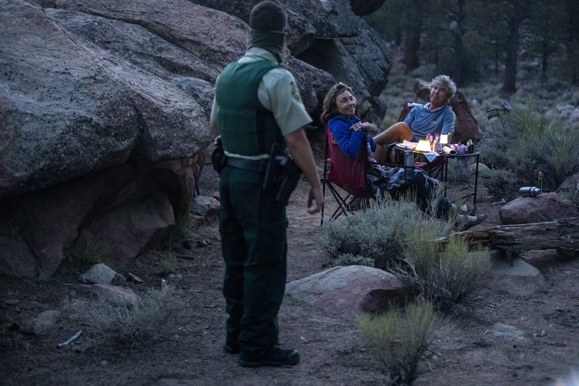 An armed ranger speaks to a couple seated at a small table in a campsite amid granite boulders and brush