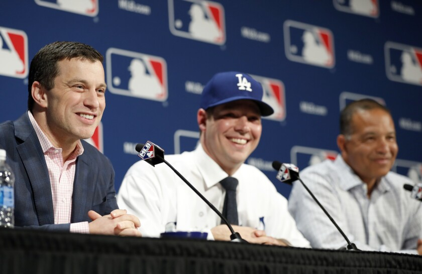 Andrew Friedman, the Dodgers' president of baseball operations, fields questions along with pitcher Rich Hill, center, and Manager Dave Roberts, right, during a Dec. 5 news conference in Oxon Hill, Md., to announce Hill's signing.