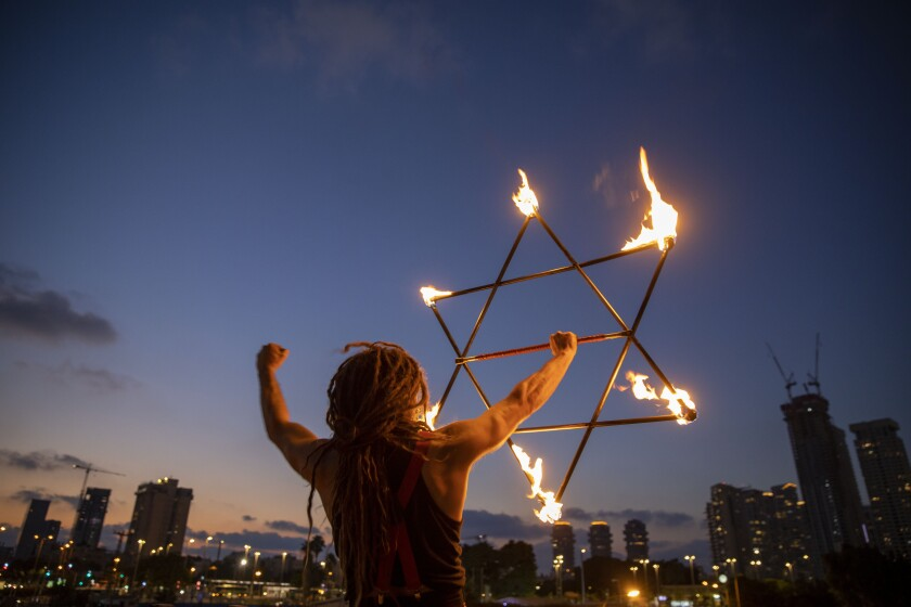 A man holds a Star of David during a protest Saturday in Tel Aviv against Israeli Prime Minister Benjamin Netanyahu.