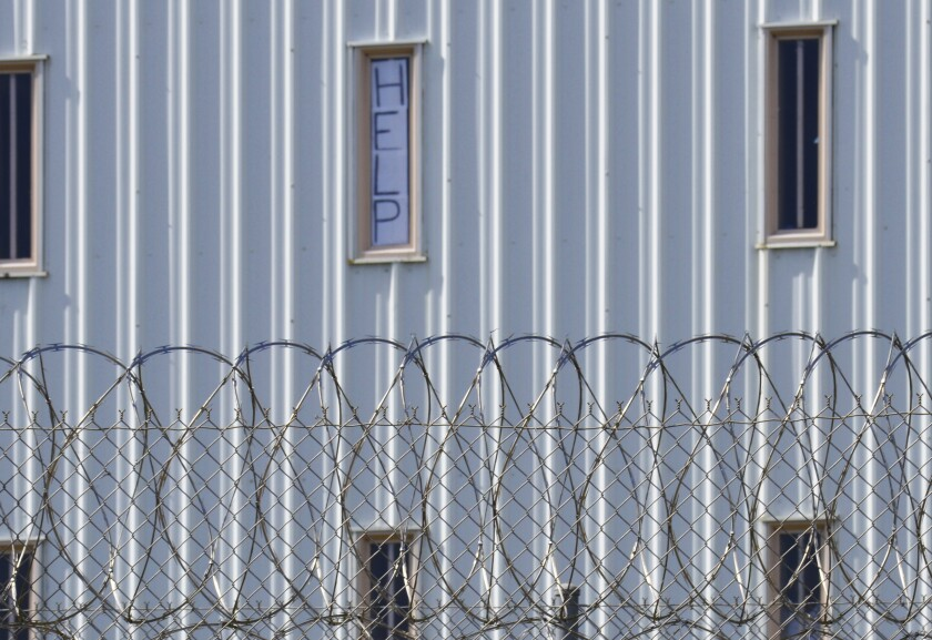 """In this Oct. 22, 2019, file photo, a sign that reads, """"HELP,"""" is posted in the window of an inmate cell during a tour along with state officials at Holman Correctional Facility in Atmore, Ala. The U.S. Department of Justice filed a lawsuit Wednesday, Dec. 9, 2020, against Alabama over conditions in the state prisons, saying the state is failing to protect male inmates from inmate-on-inmate violence and excessive force at the hands of prison staff. (AP Photo/Kim Chandler, File)"""