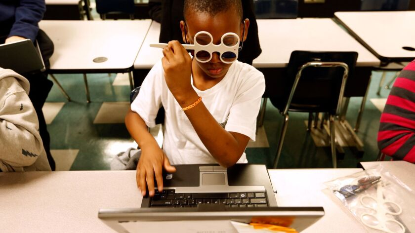 Shavalo Wooley, 8, uses 3-D glasses along with magnifying glasses while participating in a new program to improve children's reading skills by addressing problems with eye movement during the reading process at La Salle Avenue Elementary School in Los Angeles in March.