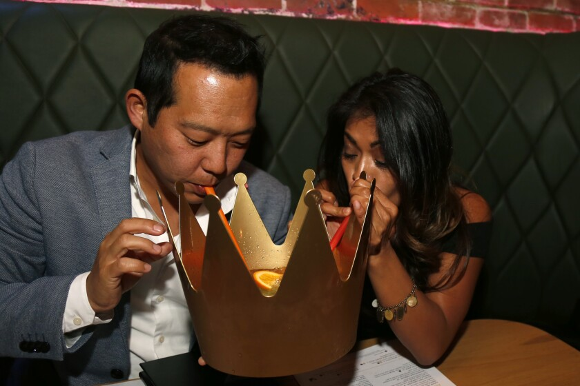 Pacific Magazine Blind Daters Jason and Megan drink from a crown at the Monkey King restaurant in downtown San Diego.