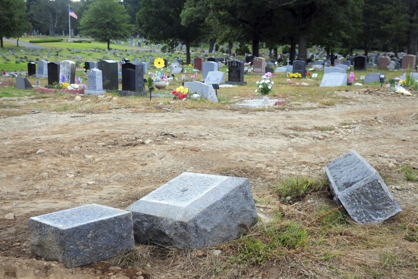 FILE - In this Oct. 2, 2018 file photo, toppled headstones rest on the ground in Park Cemetery in Bridgeport, Conn. The former caretaker of the cemetery is facing a new charge of embezzling more than $60,000 from the cemetery. Dale LaPrade, 66, was charged with first-degree larceny on Sept. 10 after a forensic audit discovered the theft of funds from Park Cemetery in Bridgeport between 2016 and 2018. (Ned Gerard/Hearst Connecticut Media via AP)