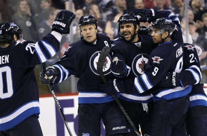 Winnipeg Jets' Olli Jokinen (12), Dustin Byfuglien (33), Grant Clitsome (24) and Evander Kane (9) celebrate Antti Miettinen's (20) goal on the New York Rangers during the second period of their NHL hockey game, Thursday, March 14, 2013,in Winnipeg, Manitoba. (AP Photo/The Canadian Press, John Woods)