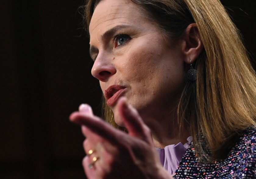 Amy Coney Barrett gestures as she testifies at her confirmation hearing.