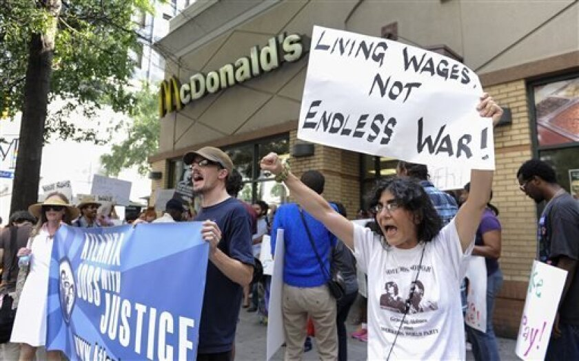 Azi Ebrahimi, right, demonstrates for higher wages for fast food industry workers during a one day strike coinciding with strikes at other fast food restaurants across the country, Thursday, Aug. 29, 2013, in Atlanta. (AP Photo/John Amis)