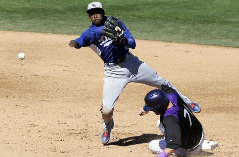 Dodgers shortstop Dee Gordon avoids Colorado's Kyle Parker on a throw to first base to complete a double play during an exhibition game this spring.