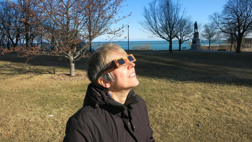 Holley Bakich observes the sun safely through approved solar glasses. These glasses, available from RainbowSymphony.com, cost $2 each, and less in quantity.