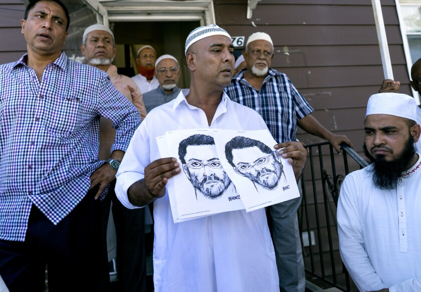 En la entrada frontal de la mezquita Al-Furqan Jame Masjid, en Queens, la ciudad de Neuva York, personas muestran el domingo 15 de agosto de 2016 un boceto del individuo que mató a tiros el día anterior al iman Maulama Akonjee y su colaborador Thara Uddinmien. Las víctimas fueron baleadas en la parte posterior de la cabeza después de que se retiraran de la mezquita al cabo de las oraciones vespertinas. (AP Photo/Craig Ruttle)