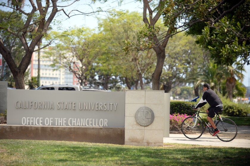 A bicyclist passes the California State University headquarters building in Long Beach.