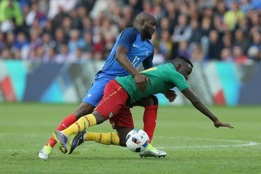 France's Lassana Diarra, left, challenges for the ball with Cameroon's Edgar Salli during a friendly soccer match between France and Cameroon at the La Beaujoire Stadium in Nantes, western France, Monday, May 30, 2016. The French squad is preparing for the EURO 2016 soccer championships which will