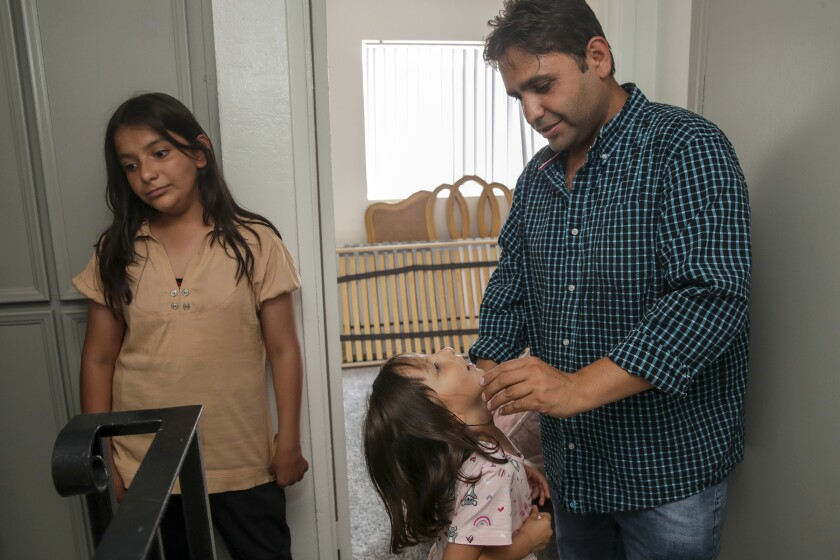 El Cajon, CA - August 23: Sayed Omer Sadat, 35, an Afghan refugee, with his two daughters Asma, 11, left, and Aqsa, 6, in his new apartment on Monday, Aug. 23, 2021 in El Cajon, CA. (Irfan Khan / Los Angeles Times)
