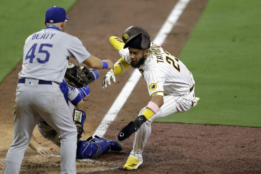 San Diego Padres' Fernando Tatis Jr. is tagged out by Dodgers catcher Will Smith during the seventh inning.
