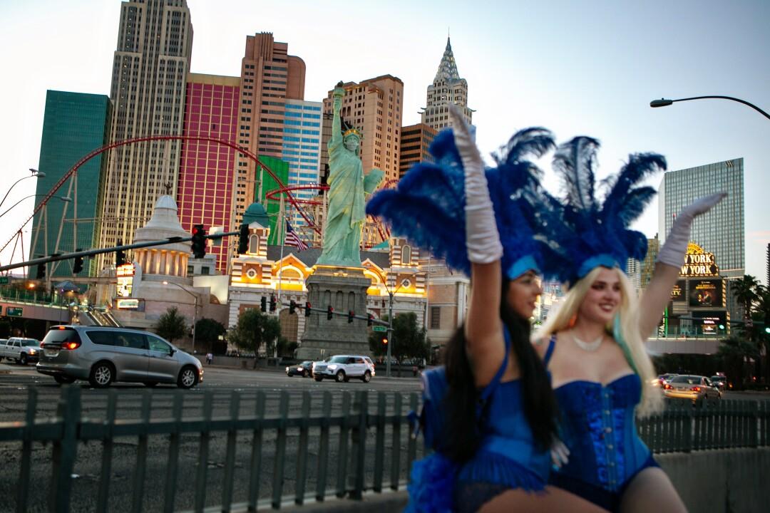 دو تظاهرات از وگاس با لباس های آبی و کلاه های پر دار دست های خود را در هوای نوار بلند می کنند