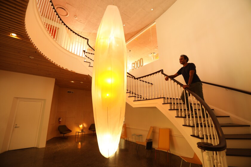 Rohan Silva stands on a curving staircase within view of a giant chandelier shaped like a cocoon.