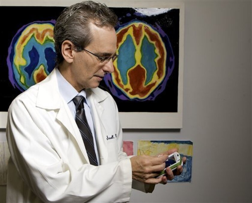 University of California, Los Angeles, Professor of Psychiatry Dr. Gary Small plays with a digital memory electronic device at his office at the Semel Institute for Neuroscience & Human Behavior in Westwood, Calif., on Monday, Dec. 1, 2008. (AP Photo/Damian Dovarganes)