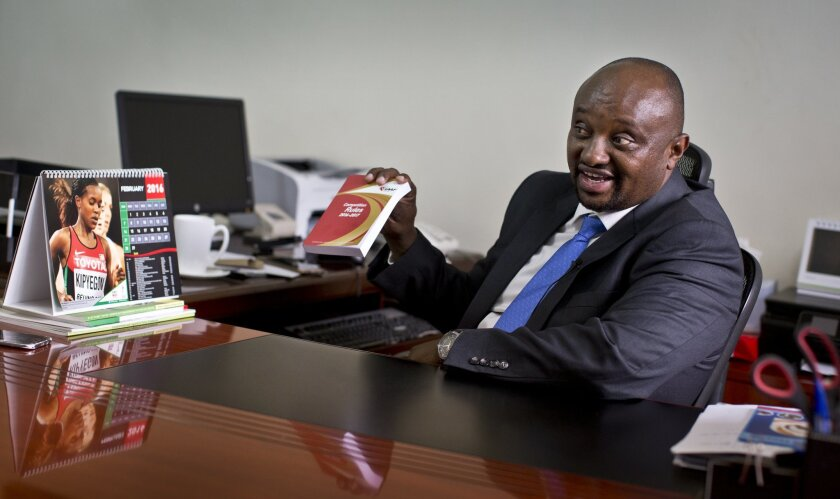 In this photo taken Monday, Feb. 8, 2016, Athletics Kenya CEO Isaac Mwangi holds up a copy of the IAAF Competition Rules book, to illustrate his denial that Athletics Kenya would have the power to shave time off athletes' bans, during an interview with The Associated Press at his office in Nairobi,