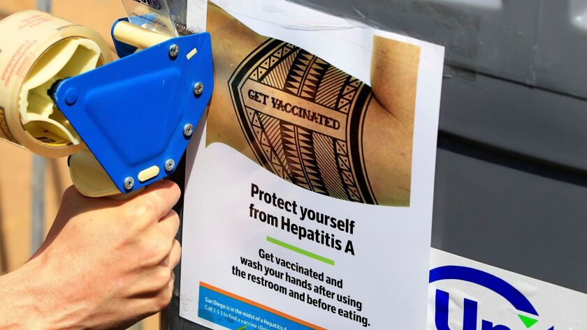 A worker tapes signage telling people to get vaccinated to protect themselves against hepatitis A on hand-washing sinks installed at the Neil Good Day Center in downtown San Diego on Sept. 1, 2017.