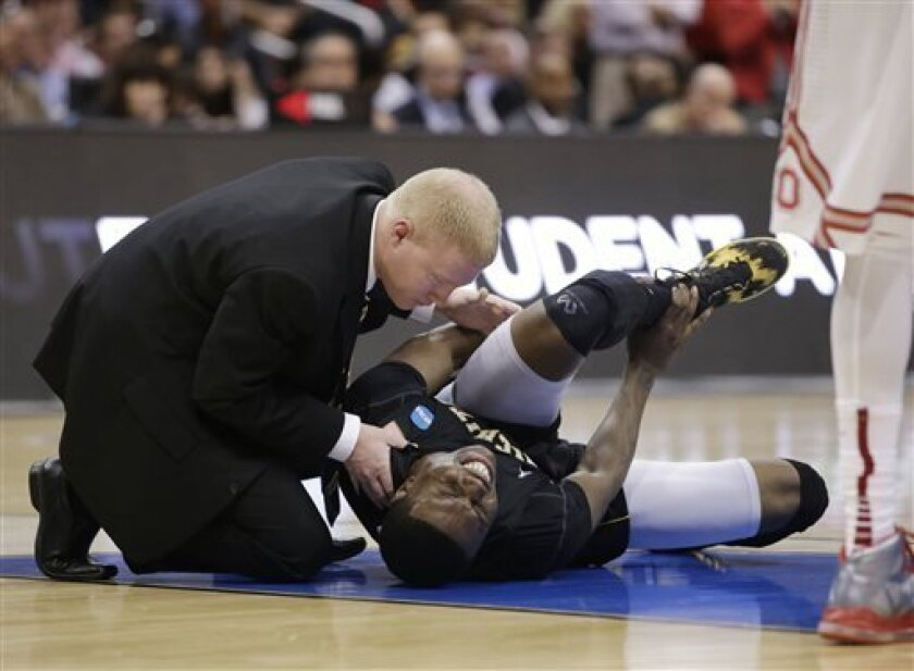 Wichita State's Cleanthony Early, right, is examined after suffering an injury during the second half of the West Regional final against Ohio State in the NCAA men's college basketball tournament, Saturday, March 30, 2013, in Los Angeles. (AP Photo/Mark J. Terrill)