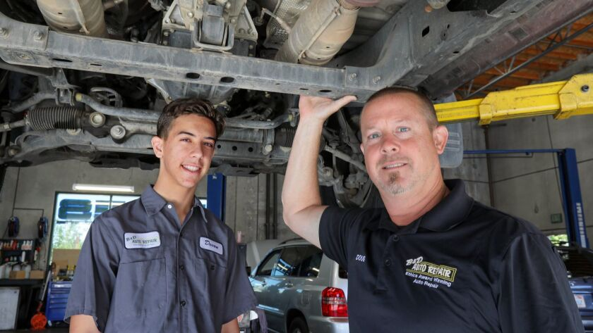 Doug Jones, owner of B&D Auto Repair, with his 17-year-old son, Devon, a high school senior who works at the Vista auto shop.