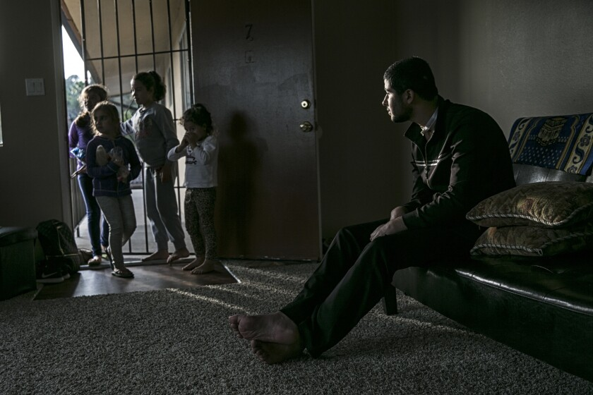Mohammad Al Kard, 21, looks on as neighborhood children drop by to play with his sisters. He suffered a head injury from a bullet wound he sustained in Syria. His family sought refuge in the U.S. in an effort to provide him the best medical care possible.