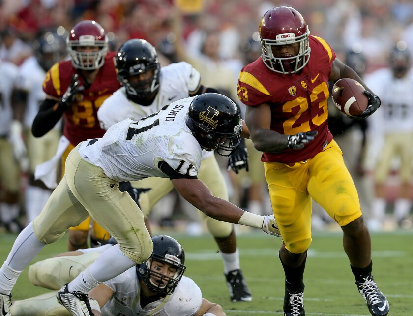 USC tailback Tre Madden eludes a tackle by Idaho strong safety Russell Siavii on the way to a touchdown in the second quarter Saturday at the Coliseum.