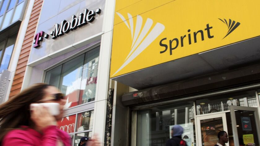 FILE - In this April 27, 2010 file photo, a woman using a cell phone walks past T-Mobile and Sprint