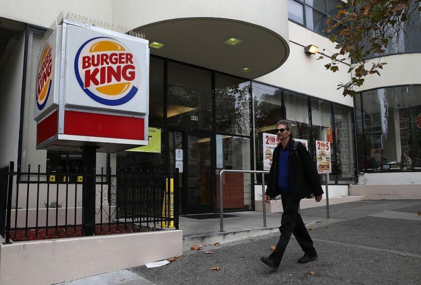 A pedestrian walks by a Burger King restaurant in San Francisco on Aug. 1.