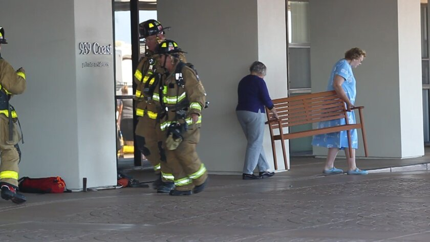 As firefighters went in to the building, two women carried a bench from the entry way of the Coast Blvd, complex out to the sidewalk to wait out the incident.