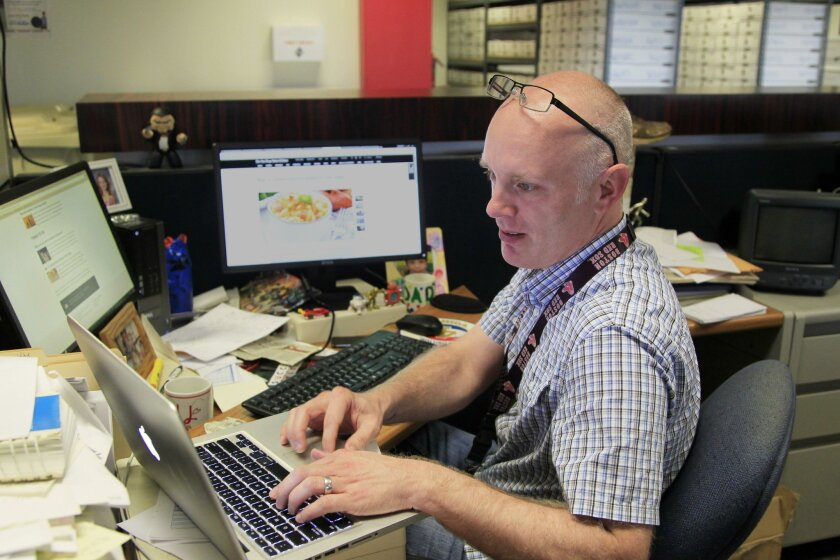 Matt Hall, public engagement director for The San Diego Union-Tribune, sits among several screens at his workspace in the newsroom.