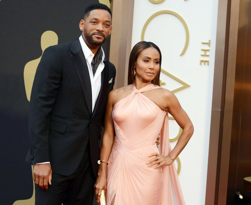 Will Smith, left, and Jada Pinkett Smith arrive at the Oscars ceremony in 2014.