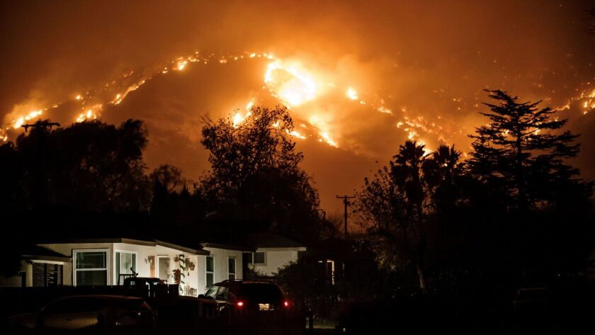 Residents watch the wildfire burn in the mountain ranges north of Ojai, Calif., on Dec. 6.