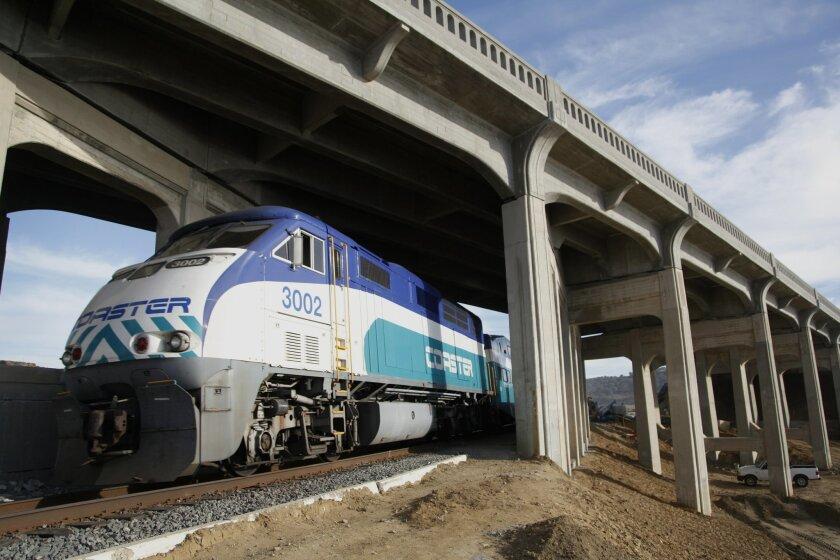 A Coaster commuter train passes under the Torrey Pines bridge amid retrofit work by Flatiron Construction Corp. on the span above. David Brooks / U-T San Diego.