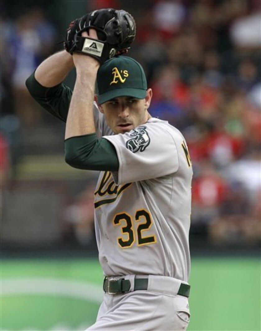 Oakland Athletics starting pitcher Brandon McCarthy (32) winds up to deliver to the Texas Rangers in the first inning of a baseball game, Saturday, July 9, 2011, in Arlington, Texas. (AP Photo/Tony Gutierrez)