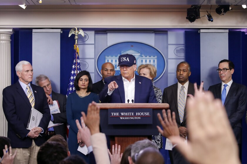 "President Trump, wearing blue ""USA"" cap, at a lectern with Mike Pence and others in front of reporters."