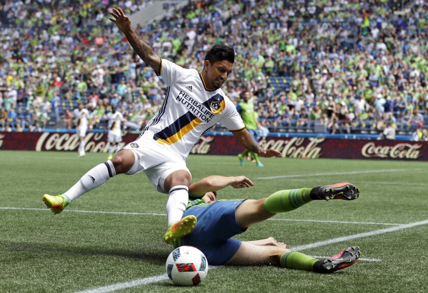 Los Angeles Galaxy defender A. J. DeLaGarza, left, goes down as he is tackled by Seattle Sounders midfielder Jordan Morris, right, in the first half of an MLS soccer match, Sunday, July 31, 2016, in Seattle. (AP Photo/Ted S. Warren)