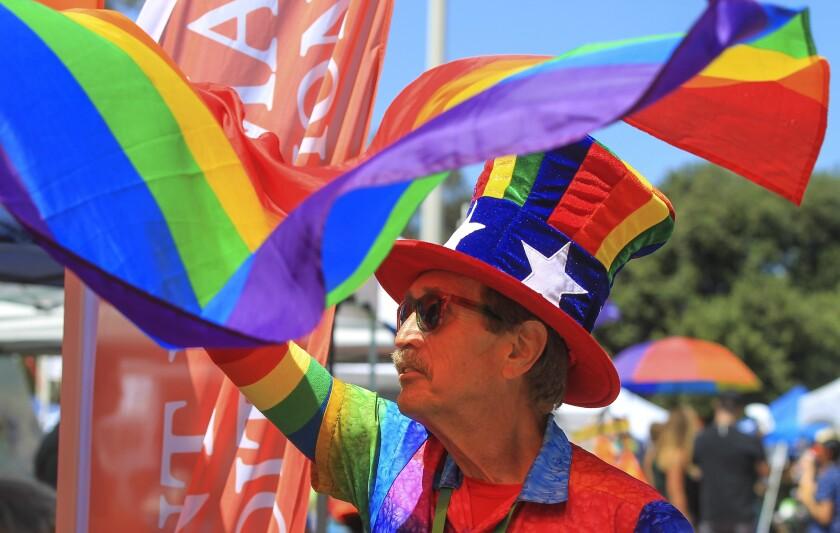 Jim Osborne, o Mister Rainbow, saluda a alguien mientras una bandera del arco iris ondea