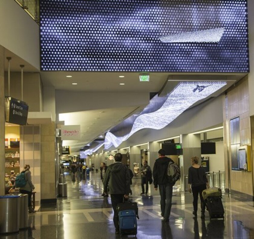 Jim Campbell's 'The Journey' is the airport's largest artwork, a 700-foot-long light ribbon of 38,000 LED pendants emitting images of swimmers. Photos by Maurice Hewitt