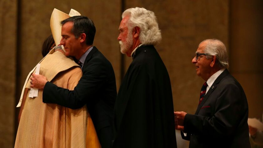 LA mayor Eric Garcetti hugs Archbishop Jose H. Gomez, following an interfaith prayer service for peace and unity at the Cathedral of Our Lady of the Angels.