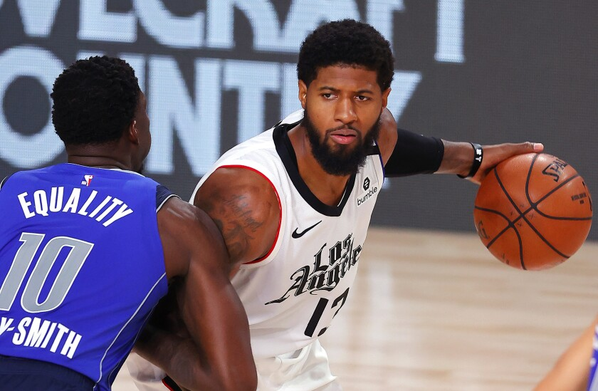 Clippers forward Paul George is defended by Dallas' Dorian Finney-Smith during Game 3 on Aug. 21, 2020.