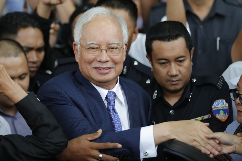 Former Malaysian Prime Minister Najib Razak is escorted from a courthouse in Kuala Lumpur last November.