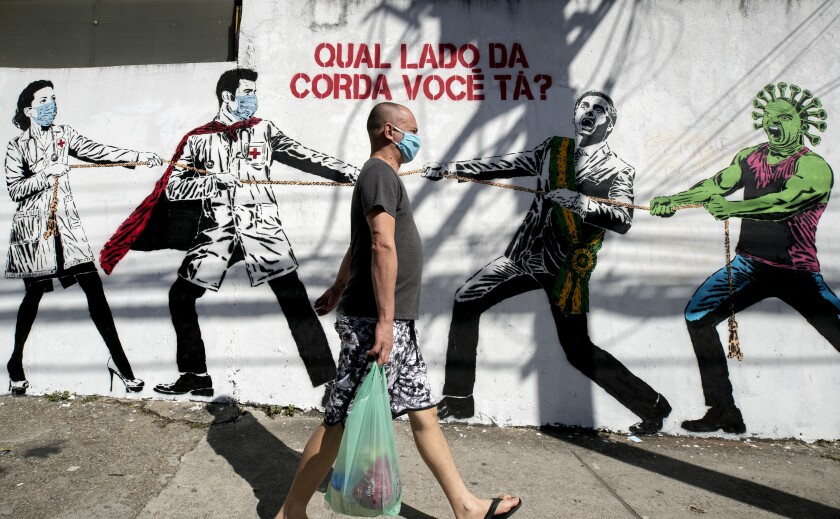 """A man, wearing a protective face mask as a measure to curb the spread of the new coronavirus, walks past a mural depicting a tug-of-war between health workers and Brazil's President Jair Bolsonaro aided by a cartoon-styled coronavirus character, with a message that reads in Portuguese: """"Which side are you on?,"""" in Sao Paulo, Brazil, Friday, June 19, 2020. (AP Photo/Andre Penner)"""