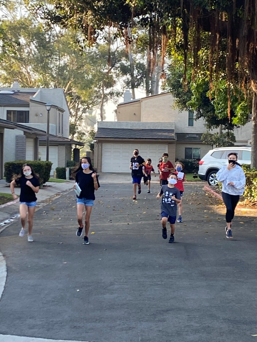 Torrey Pines and Muirlands students in a La Jolla Shores-area neighborhood run laps,.