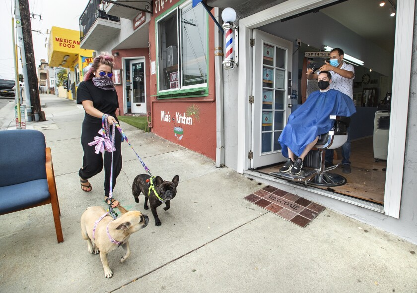 Faro Tabaja, owner of Waves Barbershop in Manhattan Beach, gives a haircut to Gene Geiser of Manhattan Beach.